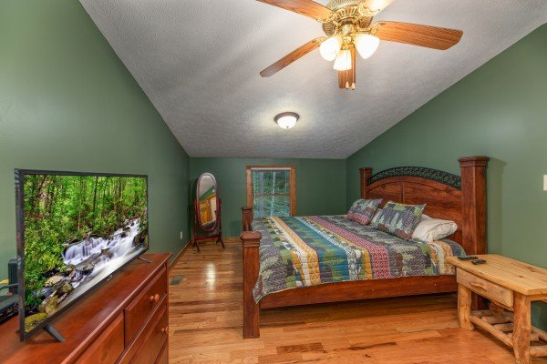 Bedroom with a king bed, lofted ceiling, TV, and dresser at Cabin by the Creekside, a 4 bedroom cabin rental located in Pigeon Forge
