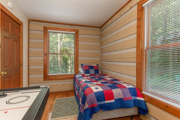 Twin bed next to an air hockey table at Cabin by the Creekside, a 4 bedroom cabin rental located in Pigeon Forge