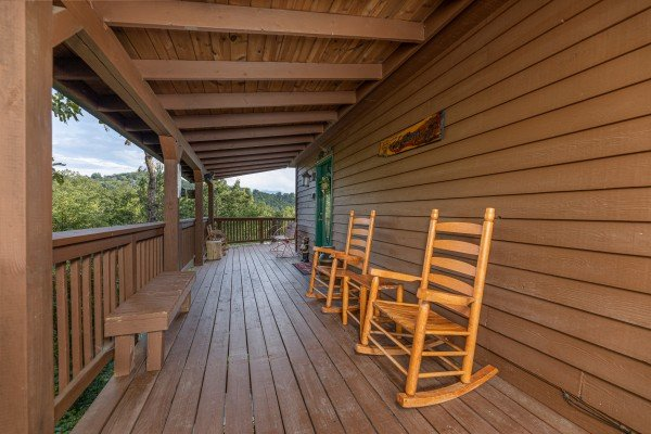 Rocking chairs and benches on a deck at Bearing Views, a 3 bedroom cabin rental located in Pigeon Forge