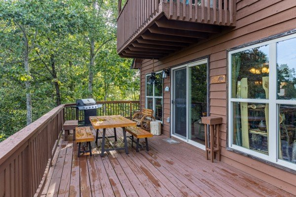 Dining table and gas grill on a deck at Bearing Views, a 3 bedroom cabin rental located in Pigeon Forge