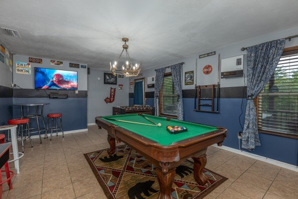 Green felt pool table and TV in a game room at Bearing Views, a 3 bedroom cabin rental located in Pigeon Forge