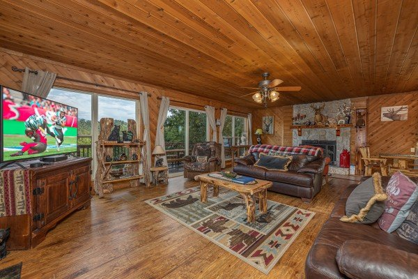 Living room with a fireplace, TV, and large windows at Bearing Views, a 3 bedroom cabin rental located in Pigeon Forge