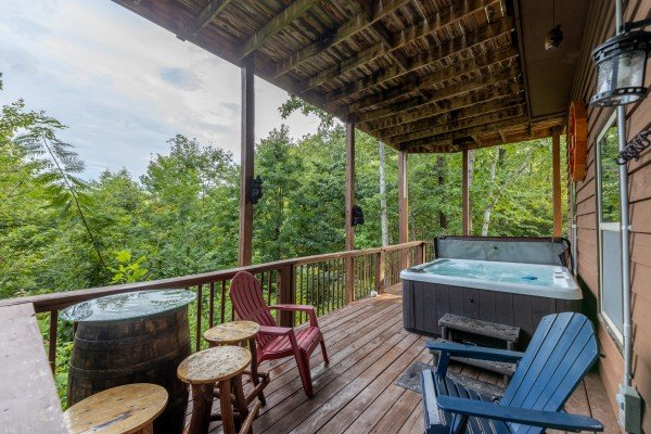 Lower deck with seating and a hot tub at Bearing Views, a 3 bedroom cabin rental located in Pigeon Forge