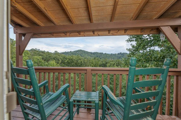 Green rocking chairs on a covered deck at Bearing Views, a 3 bedroom cabin rental located in Pigeon Forge