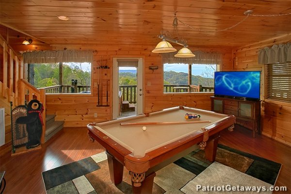Lower level game room with pool table and TV at Privacy & A View, a 3 bedroom cabin rental located in Pigeon Forge