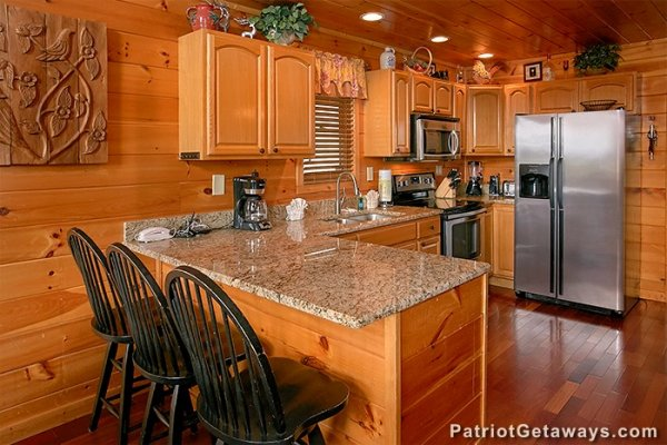 Kitchen with granite counters, stainless appliances, and counter seating at Privacy & A View, a 3 bedroom cabin rental located in Pigeon Forge
