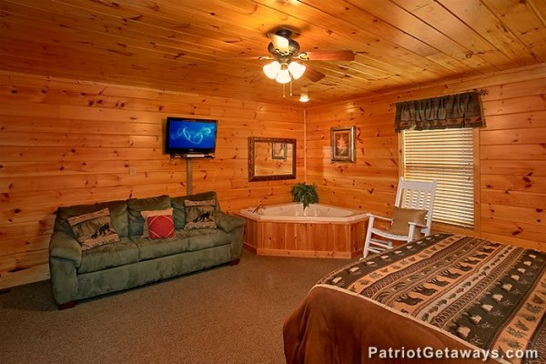 Sofa bed, corner jacuzzi, and TV in the main floor king bedroom at Privacy & A View, a 3 bedroom cabin rental located in Pigeon Forge
