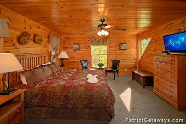 Bedroom with a king bed, dresser, and TV at Privacy & A View, a 3 bedroom cabin rental located in Pigeon Forge