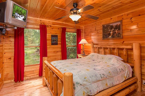 First bedroom with log bed and television at Bear View Lodge, a 2-bedroom cabin rental located in Gatlinburg