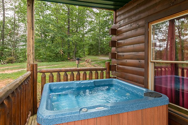 Hot tub on a covered deck at Bear View Lodge, a 2-bedroom cabin rental located in Gatlinburg