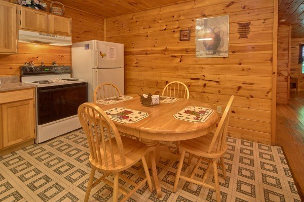 Dining space with seating for four in a kitchen with white appliances at Dream Catcher, a 1-bedroom cabin rental located in Pigeon Forge