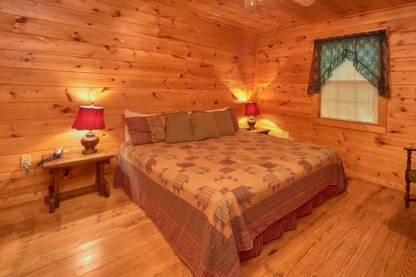 King-sized bed and two end tables at Dream Catcher, a 1-bedroom cabin rental located in Pigeon Forge