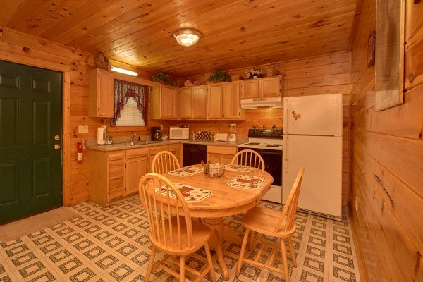 Dining table for four in the kitchen with white appliances at Dream Catcher, a 1-bedroom cabin rental located in Pigeon Forge