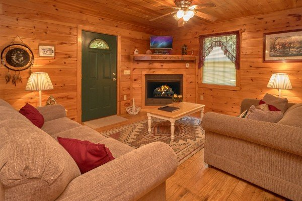 Living room with fireplace and television at Dream Catcher, a 1-bedroom cabin rental located in Pigeon Forge