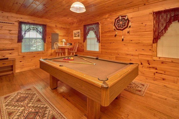 Pool table and a high top table in the game space at Dream Catcher, a 1-bedroom cabin rental located in Pigeon Forge