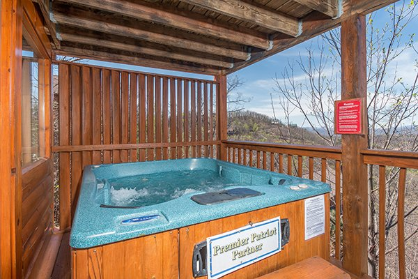 hot tub with privacy fence on a covered deck at all that jazz a 1 bedroom cabin rental located in pigeon forge
