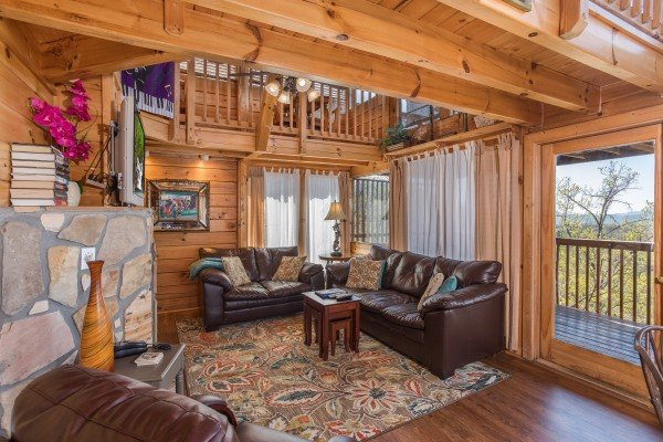 couch and loveseat with outdoor access at all that jazz a 1 bedroom cabin rental located in pigeon forge