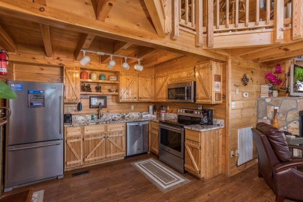 kitchen open to living room with stainless steel appliances at all that jazz a 1 bedroom cabin rental located in pigeon forge