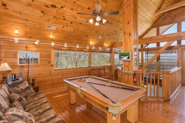 pool table with a nearby couch in the loft at all that jazz a 1 bedroom cabin rental located in pigeon forge