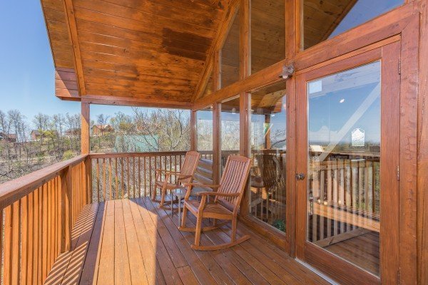 rocking chairs on a covered deck at all that jazz a 1 bedroom cabin rental located in pigeon forge