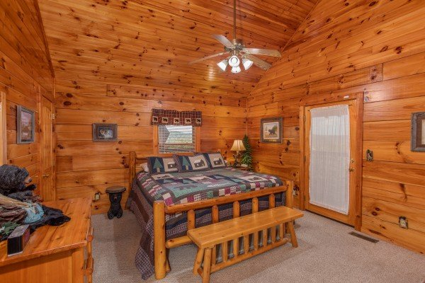 Bedroom with a log bed, bench, and vaulted ceiling at Bear Country, a 3-bedroom cabin rental located in Pigeon Forge