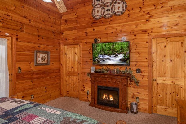 Bedroom with electric fireplace and television at Bear Country, a 3-bedroom cabin rental located in Pigeon Forge