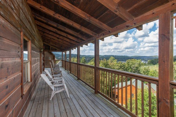 Seating and mountain views from the covered deck at Bear Country, a 3-bedroom cabin rental located in Pigeon Forge