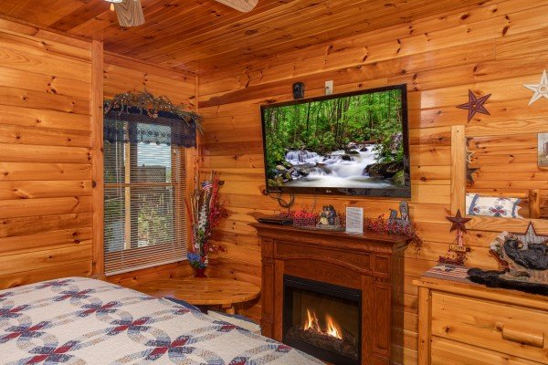 Fireplace and flat screen television in a bedroom at Bear Country, a 3-bedroom cabin rental located in Pigeon Forge