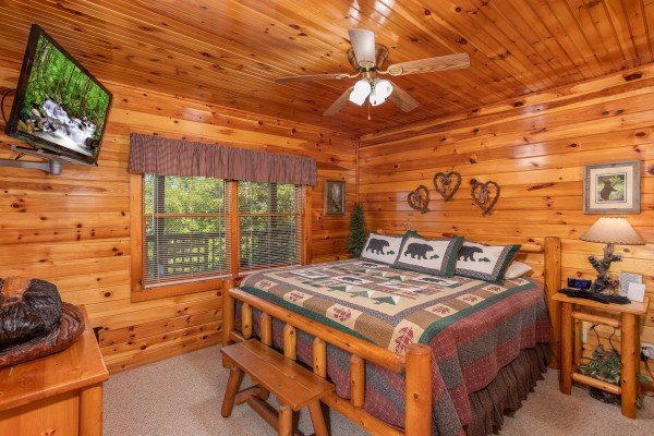 King-sized log bed with flat screen television at Bear Country, a 3-bedroom cabin rental located in Pigeon Forge