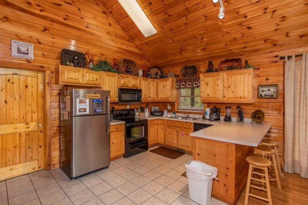 Kitchen with stainless appliances and counter seating for three at Bear Country, a 3-bedroom cabin rental located in Pigeon Forge