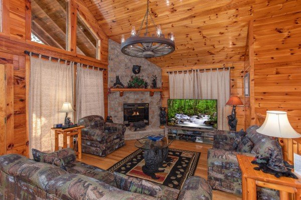 Living room with corner stone fireplace and wagon wheel chandelier at Bear Country, a 3-bedroom cabin rental located in Pigeon Forge