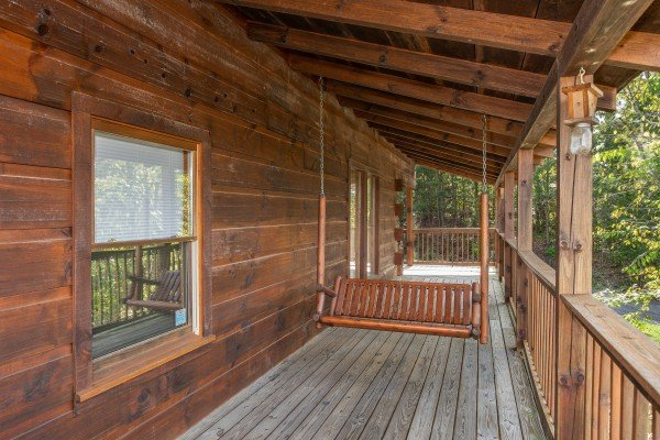 Swing on a covered porch at Bear Country, a 3-bedroom cabin rental located in Pigeon Forge