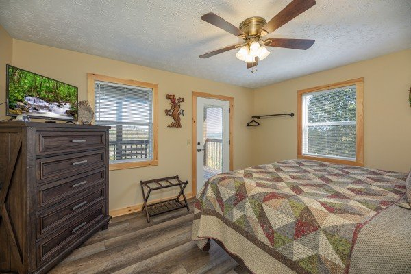 Dresser, TV, and deck access in a bedroom at Le Bear Chalet, a 7 bedroom cabin rental located in Gatlinburg