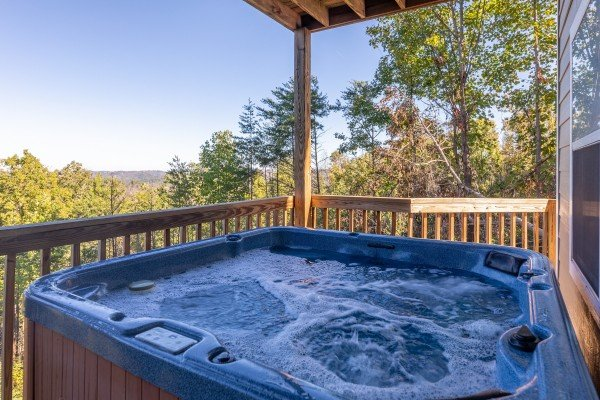 Hot tub on a covered deck at Le Bear Chalet, a 7 bedroom cabin rental located in Gatlinburg