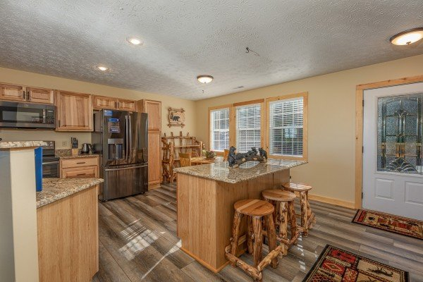 Kitchen with granite counters, stainless appliances, and a breakfast bar at Le Bear Chalet, a 7 bedroom cabin rental located in Gatlinburg