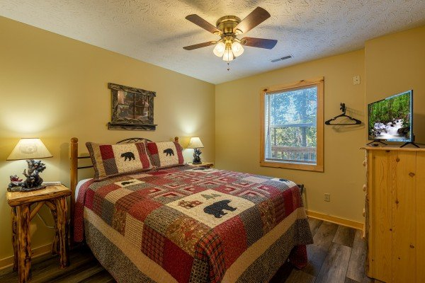 Bedroom with two night stands, lamps, dresser, and TV at Le Bear Chalet, a 7 bedroom cabin rental located in Gatlinburg