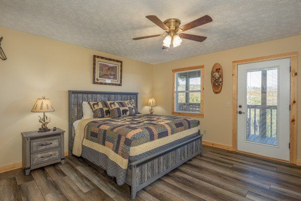 Bedroom with two night stands and lamps and deck access at Le Bear Chalet, a 7 bedroom cabin rental located in Gatlinburg