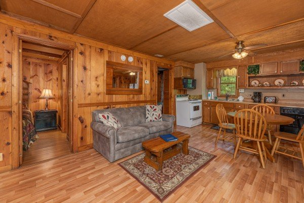 Living room with loveseat and dining table for four at Heavenly Hideaway, a 2-bedroom cabin rental located in Gatlinburg