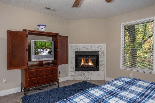 Bedroom with a TV, armoire, and fireplace at Into the Woods, a 3 bedroom cabin rental located in Pigeon Forge