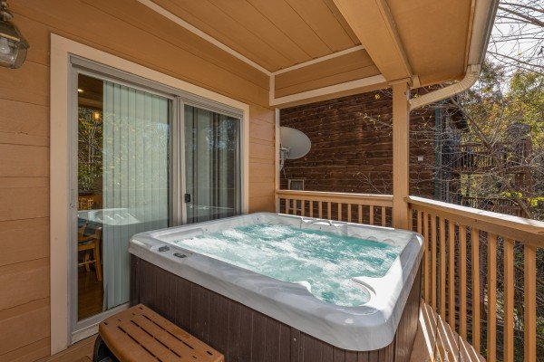 Hot tub on a covered deck at Into the Woods, a 3 bedroom cabin rental located in Pigeon Forge