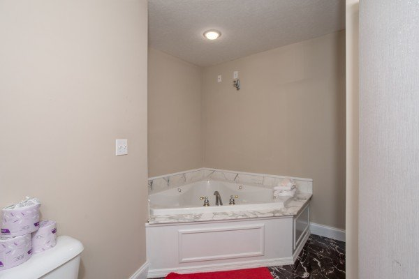 A corner jacuzzi tub in a bathroom at Into the Woods, a 3 bedroom cabin rental located in Pigeon Forge