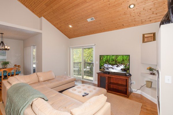 Living room with a large TV, sectional sofa, and deck access at Into the Woods, a 3 bedroom cabin rental located in Pigeon Forge