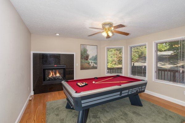 Red felted pool table with fireplace at Into the Woods, a 3 bedroom cabin rental located in Pigeon Forge