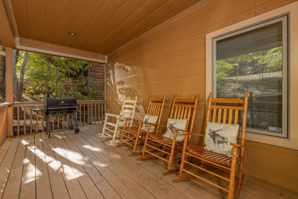 Rocking chairs and grill on a covered deck at Into the Woods, a 3 bedroom cabin rental located in Pigeon Forge