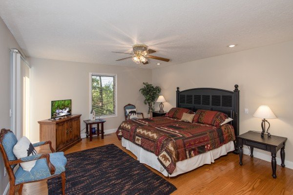 Bedroom with a king bed, TV, and sitting area at Into the Woods, a 3 bedroom cabin rental located in Pigeon Forge