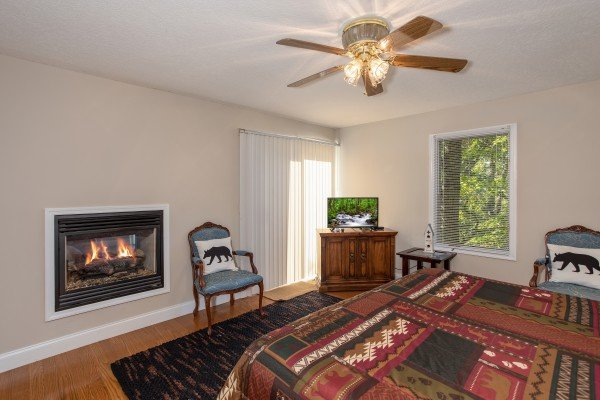 Bedroom with an in-wall fireplace, sitting area, TV, and deck access at Into the Woods, a 3 bedroom cabin rental located in Pigeon Forge