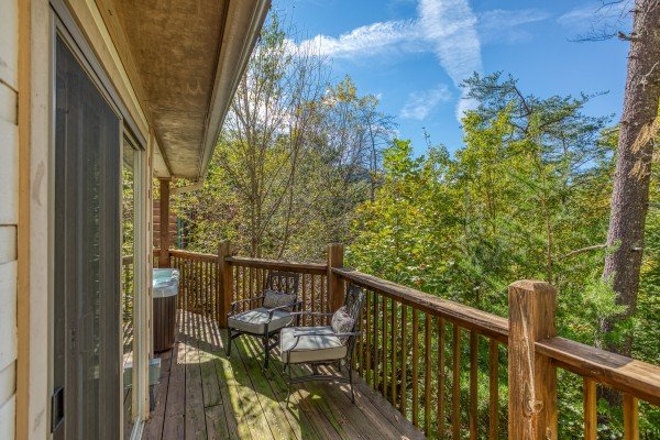 Chairs on a deck with wooded views at Into the Woods, a 3 bedroom cabin rental located in Pigeon Forge