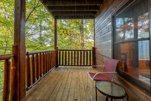 Deck chair and small table on a covered deck at Firefly Ridge, a 2 bedroom cabin rental located in Pigeon Forge
