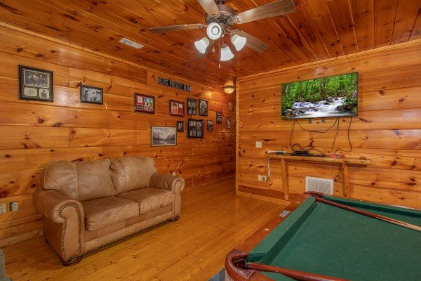 Loveseat, TV, and pool table in the game room at Firefly Ridge, a 2 bedroom cabin rental located in Pigeon Forge