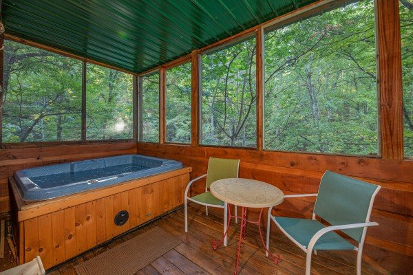 Hot tub and bistro set on a screened in porch at Firefly Ridge, a 2 bedroom cabin rental located in Pigeon Forge